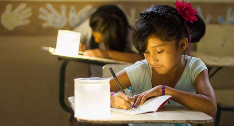 Image: Girl studying by an MPOWERD light